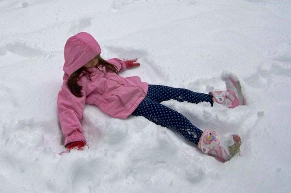 Anna makes a snow angel.
