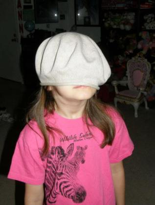 Anna with my beret over her face.