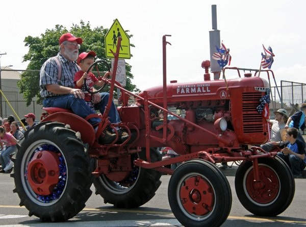 Grandpa and grandson on a tractor in the Harrisburg, OR 4th of July Parade