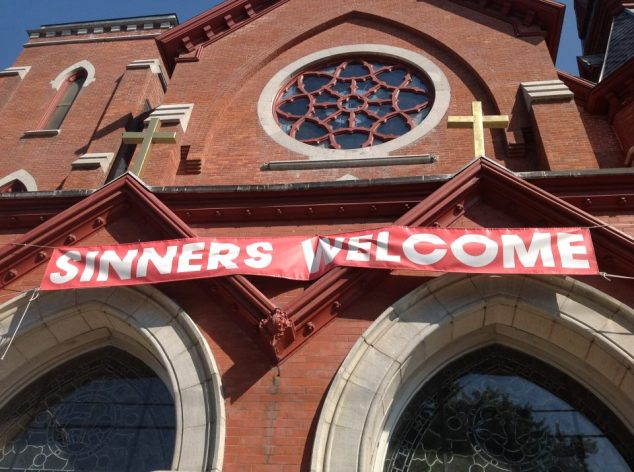 """Sinners Welcome"" banner over church door."
