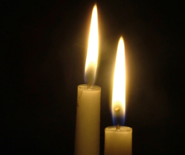 Two lit candles in darkness