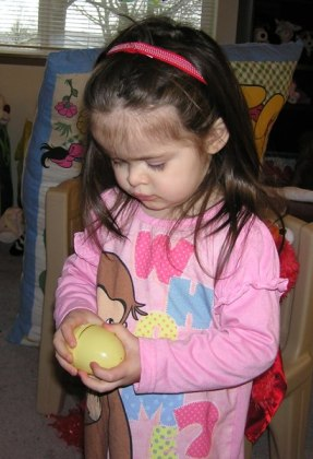 Two year old Anna opening an egg