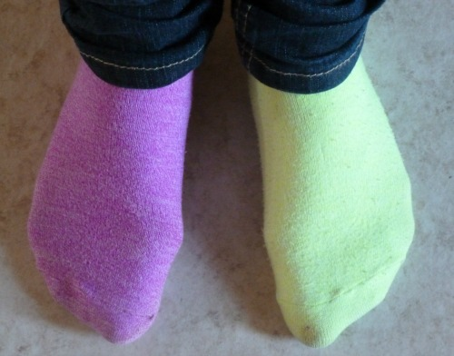 One purple sock, one light green sock.