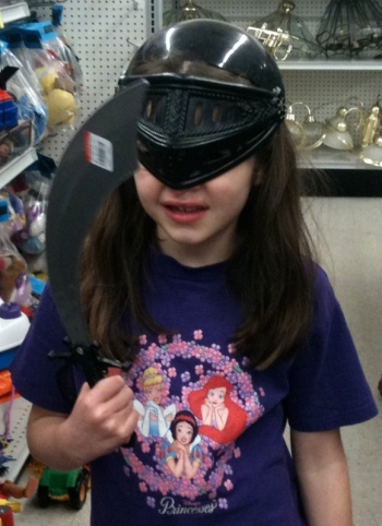 Anna in a toy helmet with sword.