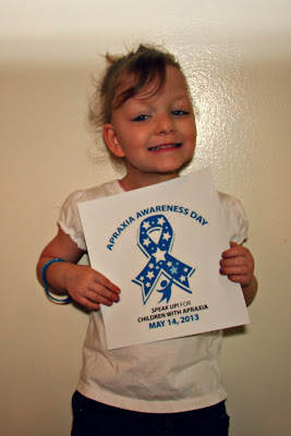 Paige holding an Apraxia Awareness Day Poster