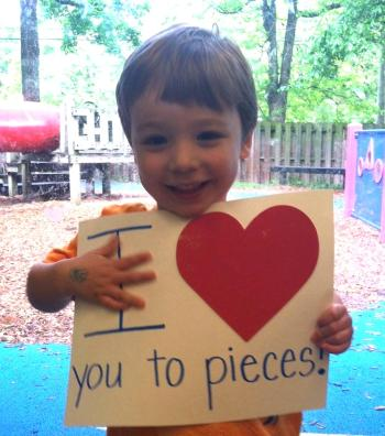 """Caleb holds """"I <3 you to pieces"""" sign"""