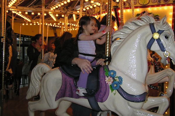 Anna rides the carousel at age two