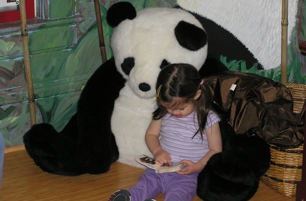 Anna reads to a giant stuffed panda toy at age two