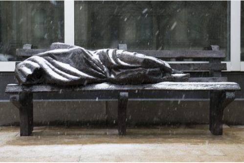 Sculpture of a homeless man under a sleeping bag on a bench.