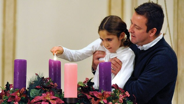 Girl lights an Advent Wreath