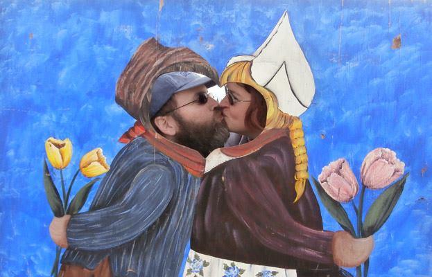 Julia and I kiss behind a wood cutout.