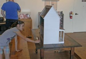 Anna looks in a dollhouse
