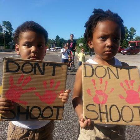 "Two black kids hold ""don't shoot"" signs."
