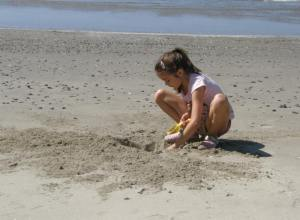 Anna digs in the sand.