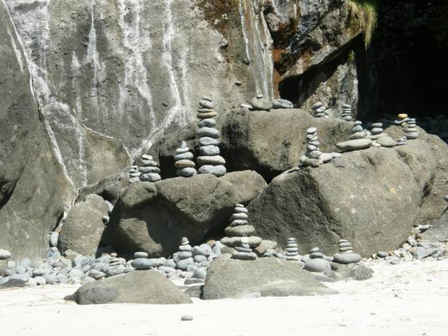 Stacks of rocks outside a cave.